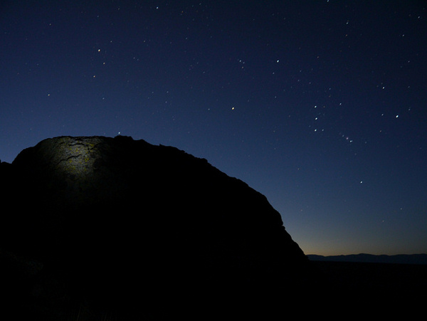 Photo: bright stars of Orion seen to the side and over a round dark hill.