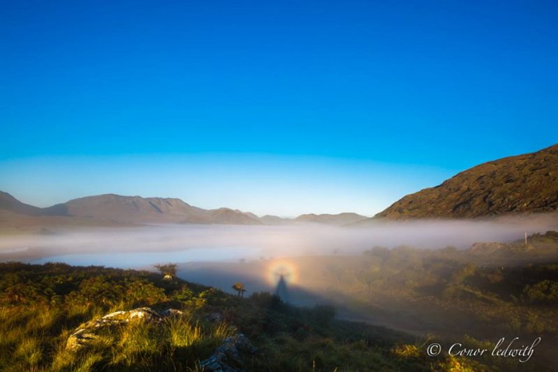 Blue sky at top, line of mist in foreground with Brocken Spectre on it against background mountains.