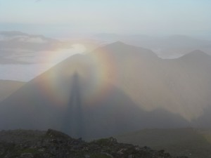 Rainbow-like halo around the shadow of a man, in a mountainous setting.