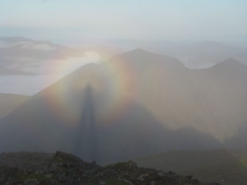 Rainbow-like halo around the elongated shadow of a man, in a dim mountainous setting.