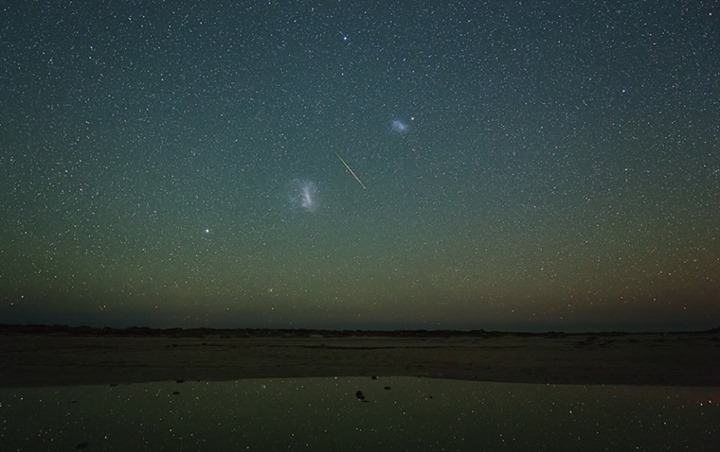 View larger. | A Perseid meteor streaks between the two Magellanic Clouds during the peak of the 2013 Perseid meteor shower. Photo by Colin Legg.