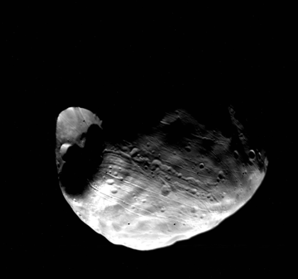 bosHere's a view of Phobos and its large Stickney Crater from Viking I.  Viking 1 Orbiter global view of the Martian satellite Phobos. The 10 km diameter Stickney crater is at the left, centered at 5 S, 55 W. The Mars facing point is at the bottom center of Phobos, and the north pole is at about 1:00 from this point. Radiating grooves and crater chains can be seen around Stickney. Phobos is roughly 20 km across in this image.