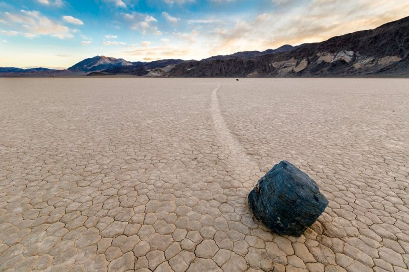 A faceted-looking black boulder with a track on a brown, cracked desert floor; mountains in background.