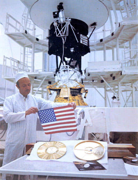Voyager project manager in 1977 was John Casani, shown here with small flag that was folded and sewed into the thermal blankets of the Voyager spacecraft before launch. Voyager 2 is behind him.  Also, shown are the famous gold records carried by the Voyager.  Read about the story of the records here.