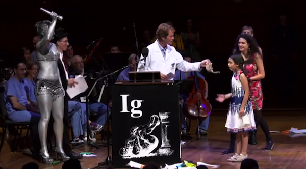 2013 Ig Nobel Archaeology Prize winner Brian Crandall presents Miss Sweetie Poo with a shrew. Looking on is a human spotlight, covered in silver body paint. Image credit: Improbable Research Inc.