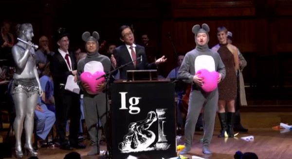 The lead author of the paper that won the Ig Nobel medical prize speaks, while his co-authors hum music from Giuseppe Verdi's opera La Traviata. Image credit: Improbable Research Inc.