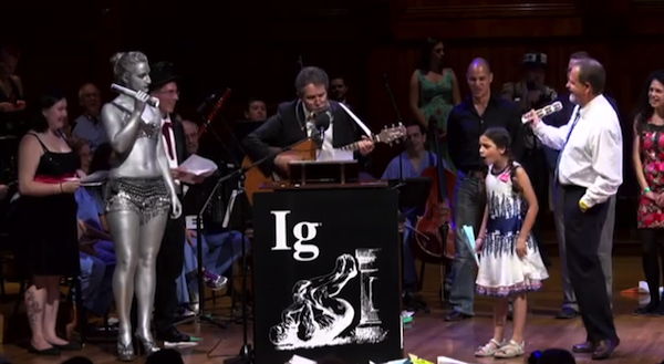 Ig Nobel Psychology prize winner Laurent Bègue tries to drown out Miss Sweetie Poo's protests. Image credit: Improbable Research Inc.