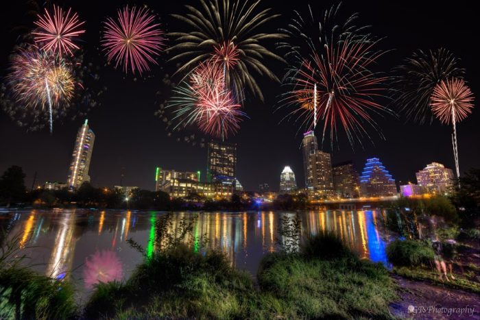 Multicolored starbursts in air above a city skyline reflected in a lake.