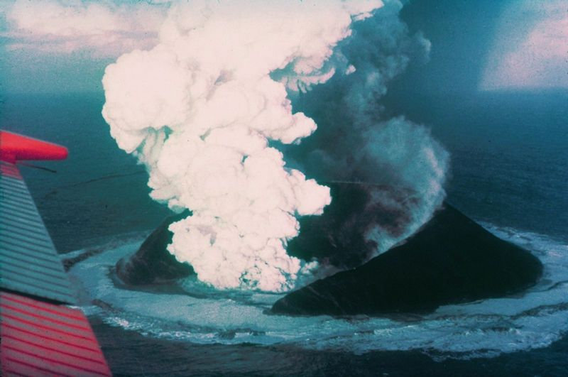 Surtsey shown in active eruption. A dark-colored island with a huge crater in the center. The crater is billowing white clouds of volcanic material and steam. Water immediately around the island is roiling from the heat. At the left side of the image is a partial view of an aircraft wing.