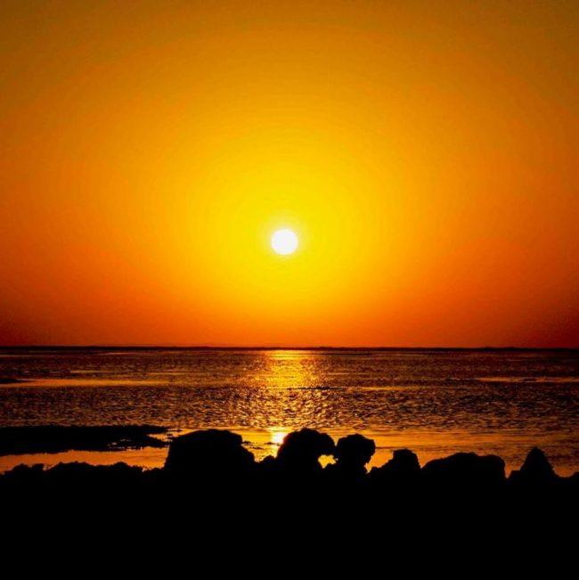 Fastest sunsets: White sun in orange-golden sky over glimmering orange sea.