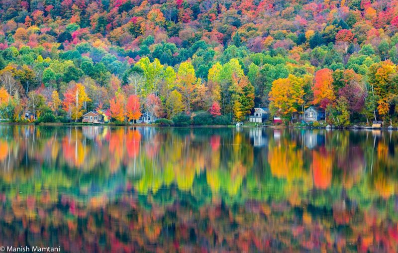 Hillside of multicolored autumn trees reflected in a still lake.