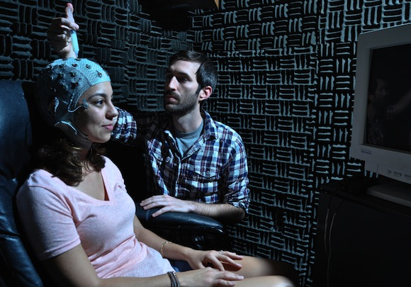 Jay Sanguinetti works with Davi Vitela to take EEG scans of her brain activity while she views a series of images for his study. Photo by Patrick McArdle/UANews