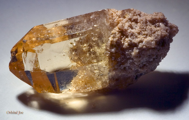 Blocky clear yellow crystal with rough pinkish matrix at one end.