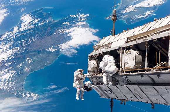 Astronauts Robert Curbeam, Jr., and Christer Fuglesang working on the International Space Station. Image Credit: NASA.