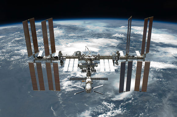 Connected cylinders with many rectangular wing-like solar panels extending from them. Earth from orbit in background.