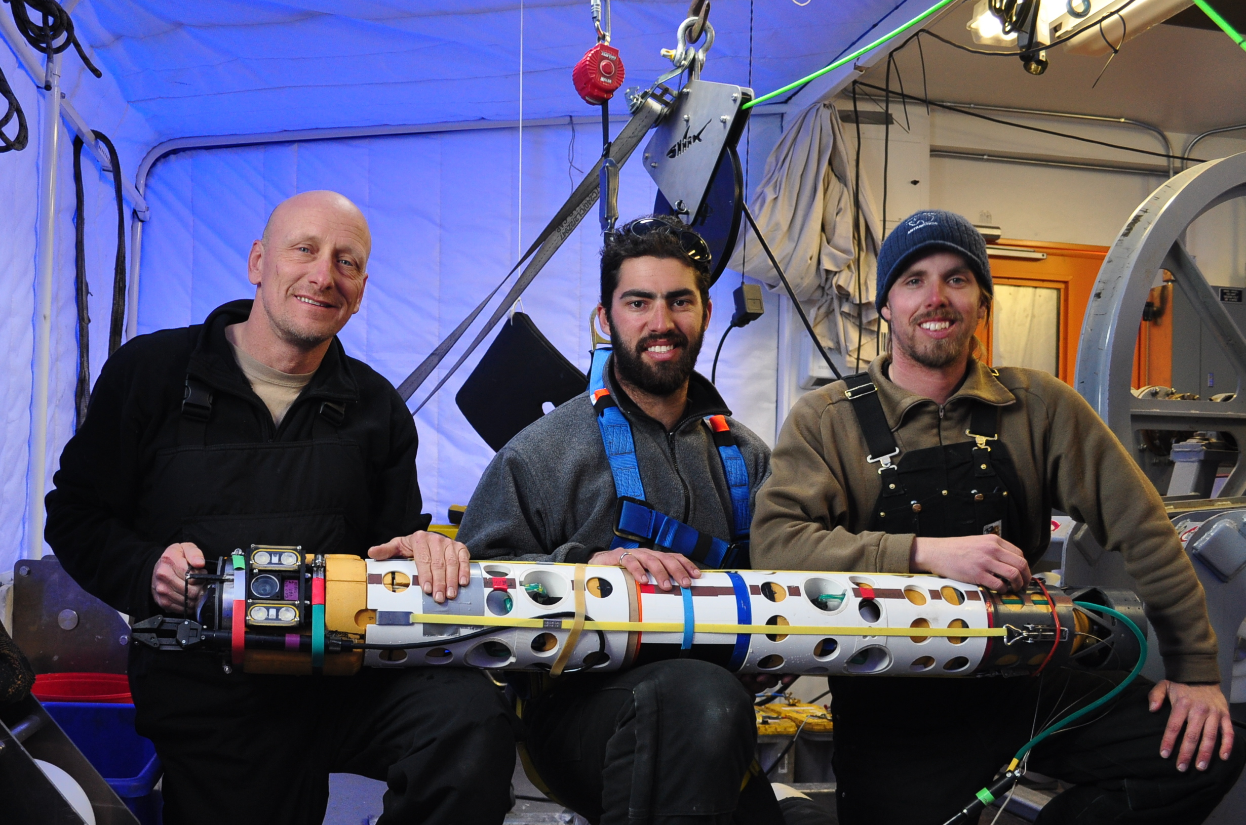 Robot deployment team engineers Bob Zook, Paul Mahecek, and Dustin Carroll, seen here holding the underwater robot that captured images of the ice anemones. Image credit: Dr. Frank R. Rack, ANDRILL Science Management Office, University of Nebraska-Lincoln.
