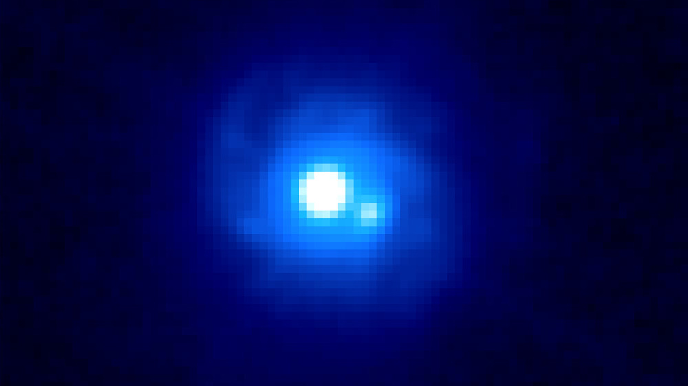 This Hubble image of the gravitational lens B0218+357 reveals two bright sources separated by about a third of an arcsecond, each an image of the background blazar. Faint spiral arms belonging to the lensing galaxy also can be seen. B0218+357 boasts the smallest separation of lensed images currently known. The A image (4 o'clock position) is where changes are first observed and is significantly fainter than the B image (center) at optical wavelengths.