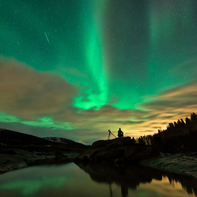 silhouetted man watching meteor against green aurora
