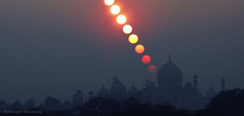 Row of suns descending over dimly silhouetted Arabic-style domes and towers of Taj Mahal.