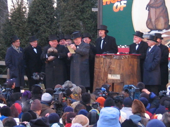 Men in dark winter coats and top hats, one holding a groundhog; crowd watching.