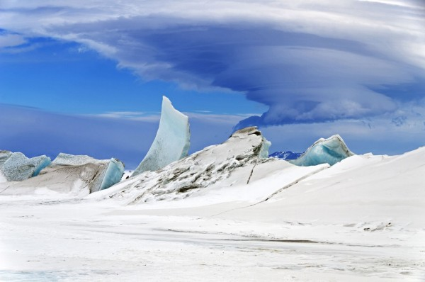 Immense mushroom-shaped lenticular cloud over large ice formations.