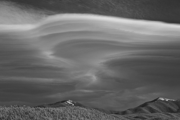 Grayscale multiple lenticular clouds over 2 ice-capped mountains.