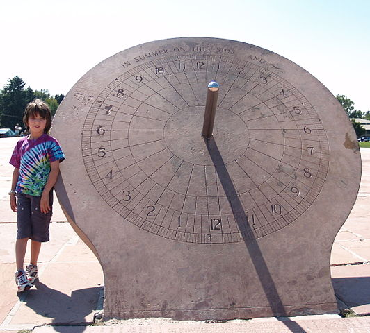 Equatorial sundial at Denver's Crammer Park, when it is a little past 11:00 a.m. by the sun. (The shadow moves clockwise, with the afternoon hours on the left.) Click here for the equation of time in 2015.
