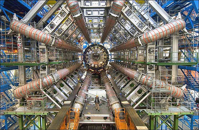 Huge machine, tiny person standing in it for scale, with giant radial pipes coming out from the center.