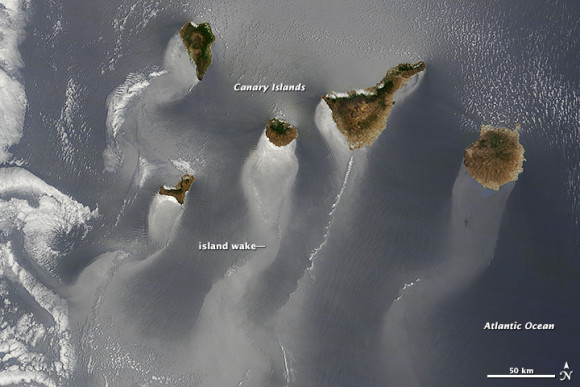 Wavy, windsock-like tails stretch to the southwest from each of the islands. The patterns are likely the result of winds roughening or smoothing the water surface in different places.