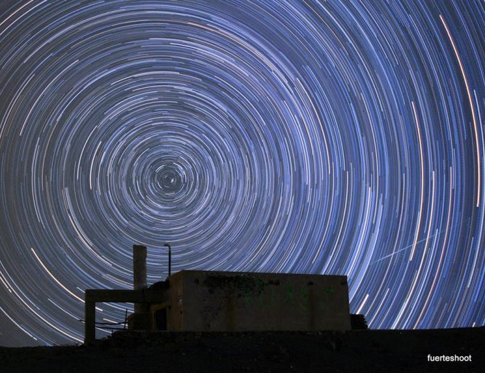 Concentric circles of star trails with a meteor streaking across.