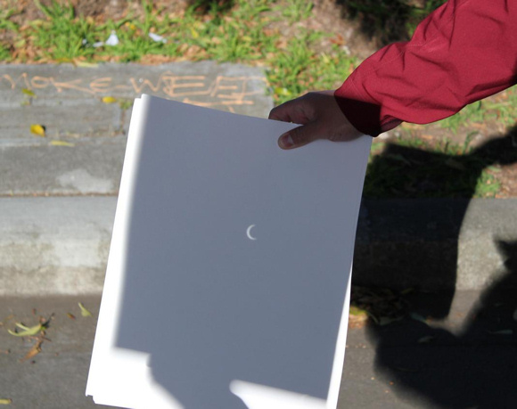 A man's hand holding a piece of paper with a small bright crescent on it.