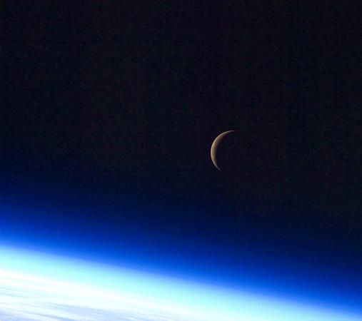 Thin crescent moon with part of Earth from orbit showing below.