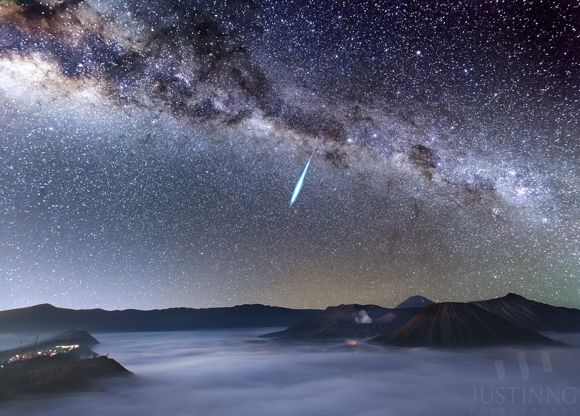 Very bright meteor streak against Milky Was, above misty valley in crater of mountain.
