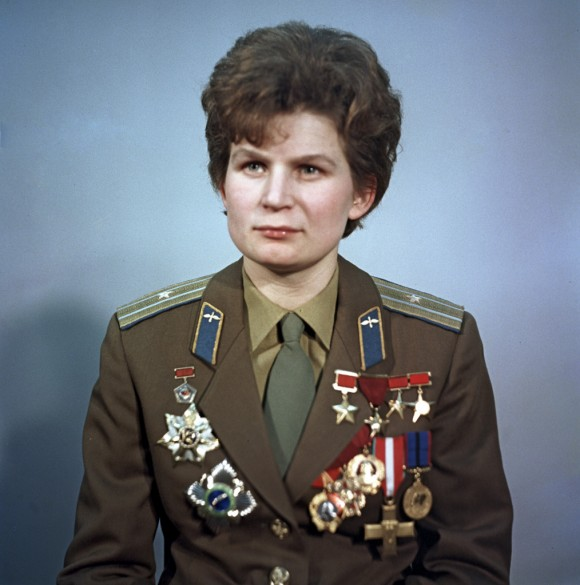 Woman in military uniform with bluish background.