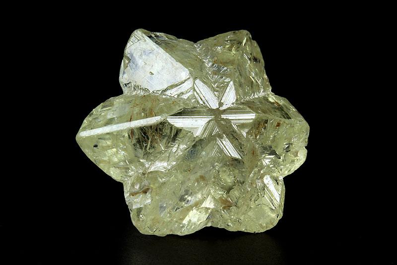 A glittering, greenish, six-sided starlike natural crystal.