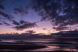 A twilight beach scene, with scattered clouds, and a tiny crescent moon.