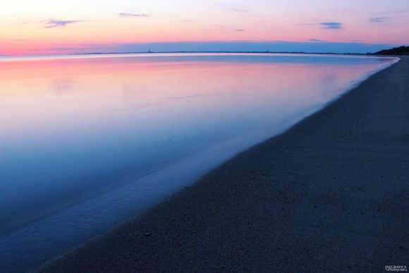 Pink and blue sunset reflected in ocean.
