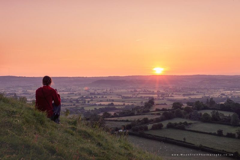 Man sitting on high hill overlooking wide landscape with hedgerows and fields, sun near horizon.