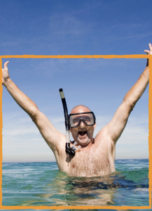 Man in scuba gear, standing in ocean-water up to his chest, with arms upraised.
