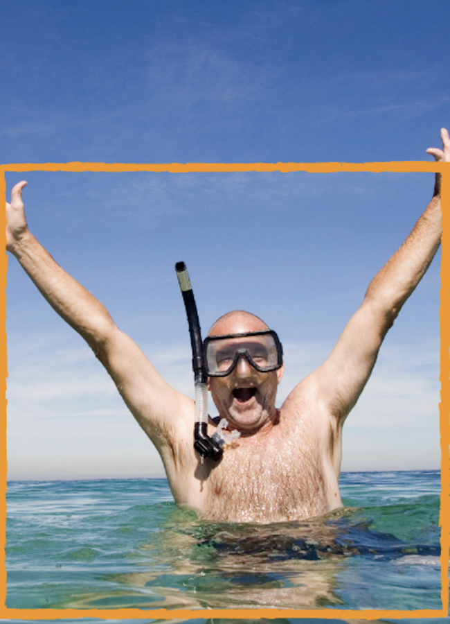 Half-naked man with snorkel, standing in ocean water up to his chest, with arms upraised.