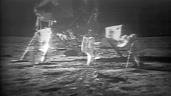 Fuzzy black and white photo of lunar lander with astronaut and flag in front of it.
