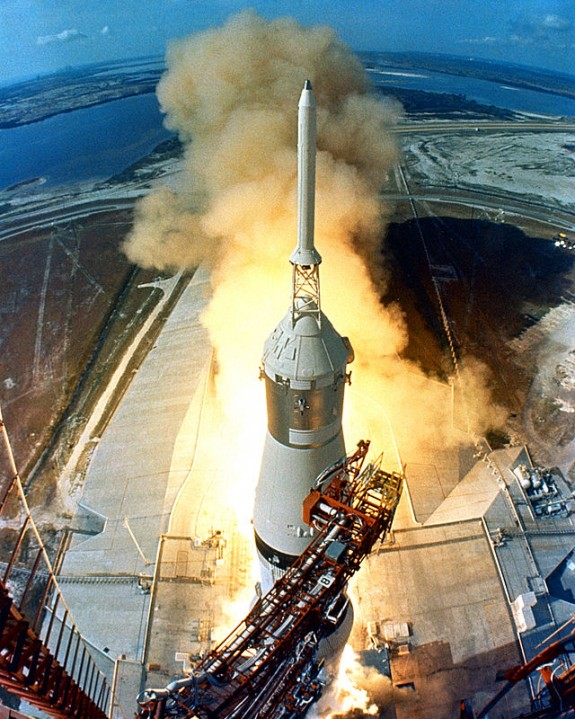 View from above of immensely tall rocket with flame and smoke far below.