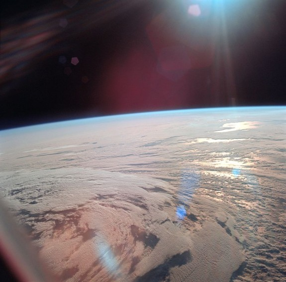 Orbital view of mostly clouded Earth with sun glinting from sea, blue along curved horizon, black sky.