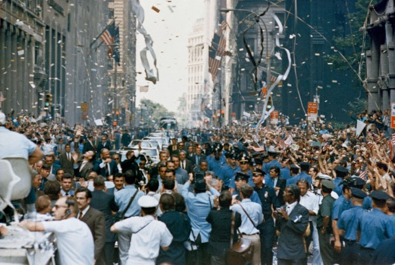 Crowds of people in street between tall buildings with air full of paper bits and streamers.