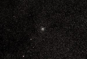 Tight collection of whitish stars at the center of the image, with very sparse whitish stars over a wide field of view.