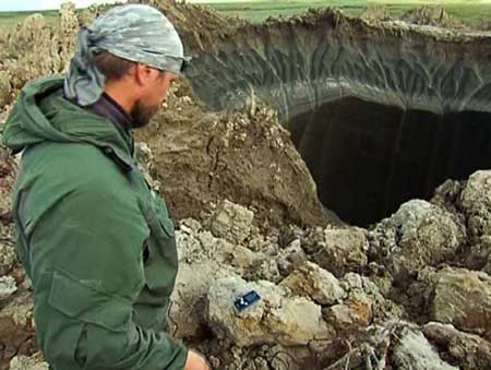 Andrei Plekhanov, senior researcher at the Scientific Research Centre of the Arctic, stands at the first large crater, discovered recently in the Yamalo-Nenets Autonomous Okrug region of northern Russia.  Image via China Post.