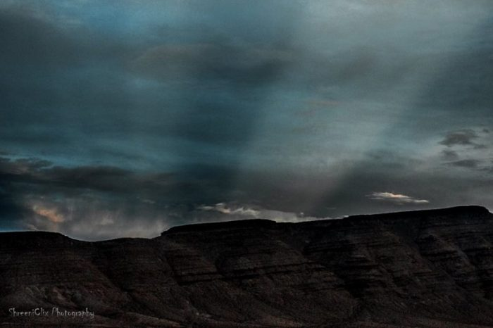 Wide light rays through clouds over a mountain landscape.