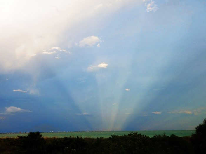 Anticrepuscular rays opposite the setting sun off the Florida Gulf Coast of the United States.  Photo by Wojtow via Wikimedia Commons.