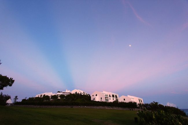 Pink rays converging over white buildings on a hilltop with small moon visible.