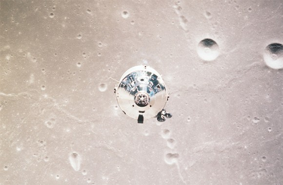 End view of shiny, metallic conical module against light tan lunar surface with craters.